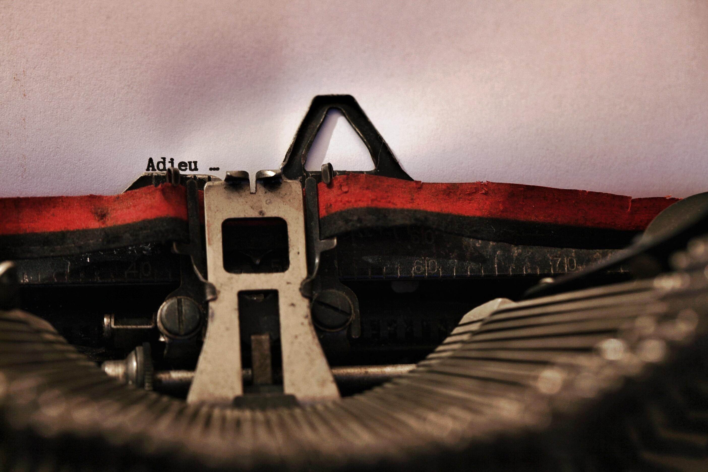 """Photographie montrant le mot """"Adieu"""" tapé à la machine à écrire."""