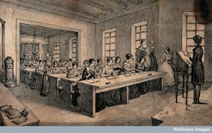 A classroom with children sitting at long tables. Lithograph J.B. Sonde. Credit: Wellcome Library, London.