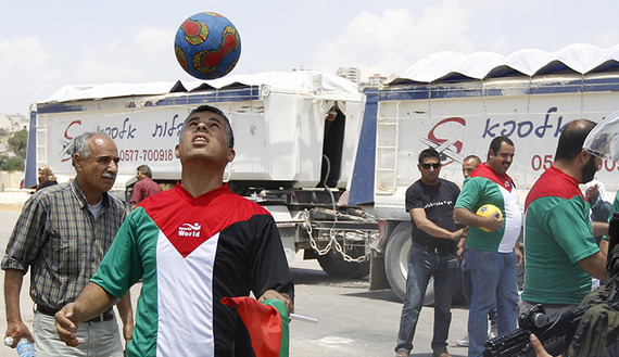 A Palestinian protester holding a Palestinian flag heads a soccer ball next to Israeli border police during a demonstration outside Israel's Ofer military prison