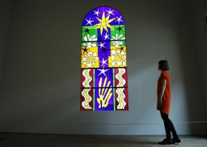 672210-an-employee-poses-with-a-stained-glass-designed-by-henri-matisse-at-the-tate-modern-gallery-in-londo
