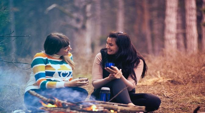 Deux femmes parlant autour d'un feu de camp