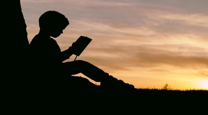 Enfant lisant un livre dans le soleil couchant
