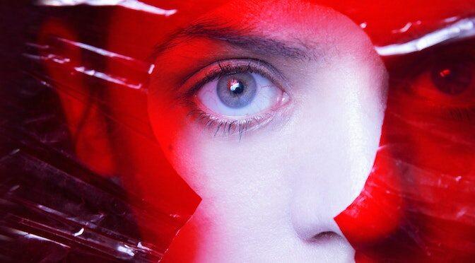 Visage de femme derrière un voile en plastique rouge