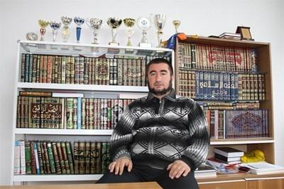 Imam principal de la mosquée dans son bureau posant devant ses coupes de football et ses livres religieux pour le journal « 24 heures » en 2014 –