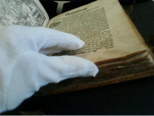 Manejando un impreso del siglo XVI con guantes.Foto procedente de Twitter