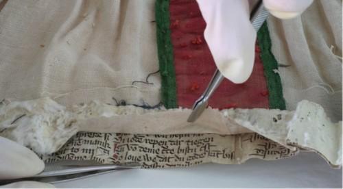 Fragmento de pergaminos en el dobladillo de el vestido de una figura devocionalFoto procedente de Lähnemann 2013: 72, il. 64