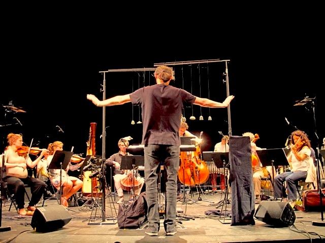 Marc Desmons dirige l'orchestre et utilise le dispositif technologique.