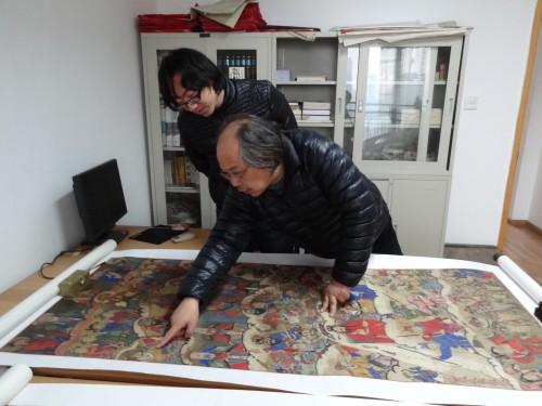 Li Yuanguo montrant un rouleau de sa collection