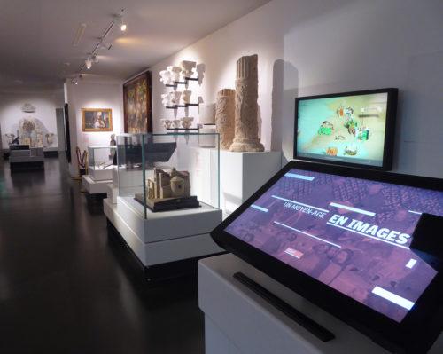 Deux écrans au premier plan donnent à voir les dispositifs pédagogiques de vulgarisation scientifique sur la Marseille médiévale. La perspective fait glisser le regard sur les objets et tableaux de l'époque exposés à l'arrière-plan.