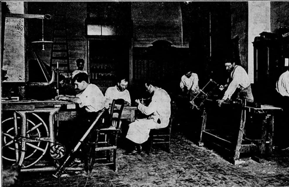Plusieurs mutilés de guerre sont dans un atelier en train d'apprendre la menuiserie