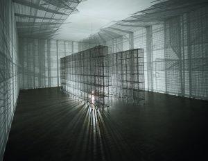 """36 unités de casiers en treillis métallique composant par leur juxtaposition une structure en forme de """"U"""". Une ampoule, suspendue au bout d'un fil au centre de la structure, varie lentement de hauteur, actionnée par un moteur électrique et projette des ombres mobiles en fonction de son mouvement. Le spectateur est entrainé dans l'activité de l'oeuvre : les ombres de son corps deviennent partie intégrante de la pièce."""
