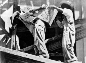 Tina MODOTTI (1896-1942), Ouvriers transportant des blocs de pierre sur leur dos pour la construction d'un immeuble, vers 1926-1927, épreuve gélatino-argentique, 7,5 x 10,2 cm, Collection Ruth et Labrie Ritchie