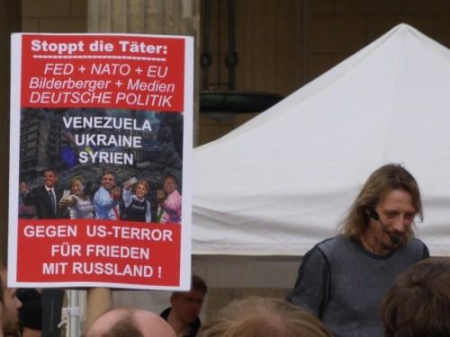 """Lars Mährholz bei Berliner Montagsmahnwache im April 2014. Neben ihm ist ein Plakat zu sehen: """"Stoppt die Täter: / FED + NATO + EU / Bilderberger + Medien / DEUTSCHE POLITIK / Venezuela / Ukraine / Syrien / Gegen US-Terror / Für Frieden / Mit Russland!"""" (Autor: Anonym, https://linksunten.indymedia.org/de/node/110794, Creative Commons Lizenz: http://creativecommons.org/licenses/by-nc-sa/2.0/de/)"""