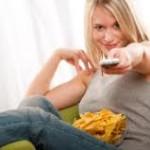 Jeune femme pointant la télécommande vers nous, un bol de chips surles genoux