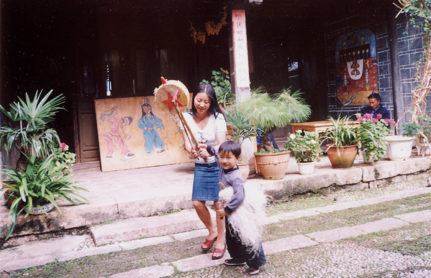 A photo of He Qin 和沁 playing with her son in the courtyard of the Naxi Culture Education Association, Lijiang (2002)