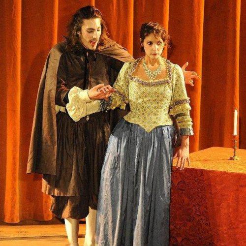Tartuffe et Elmire sont tous deux face au public, devant la table où se cache Orgon.