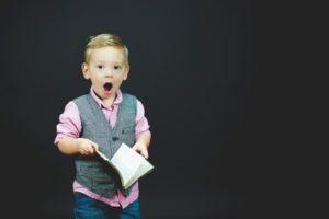 enfant scandalisé avec un livre entre les mains