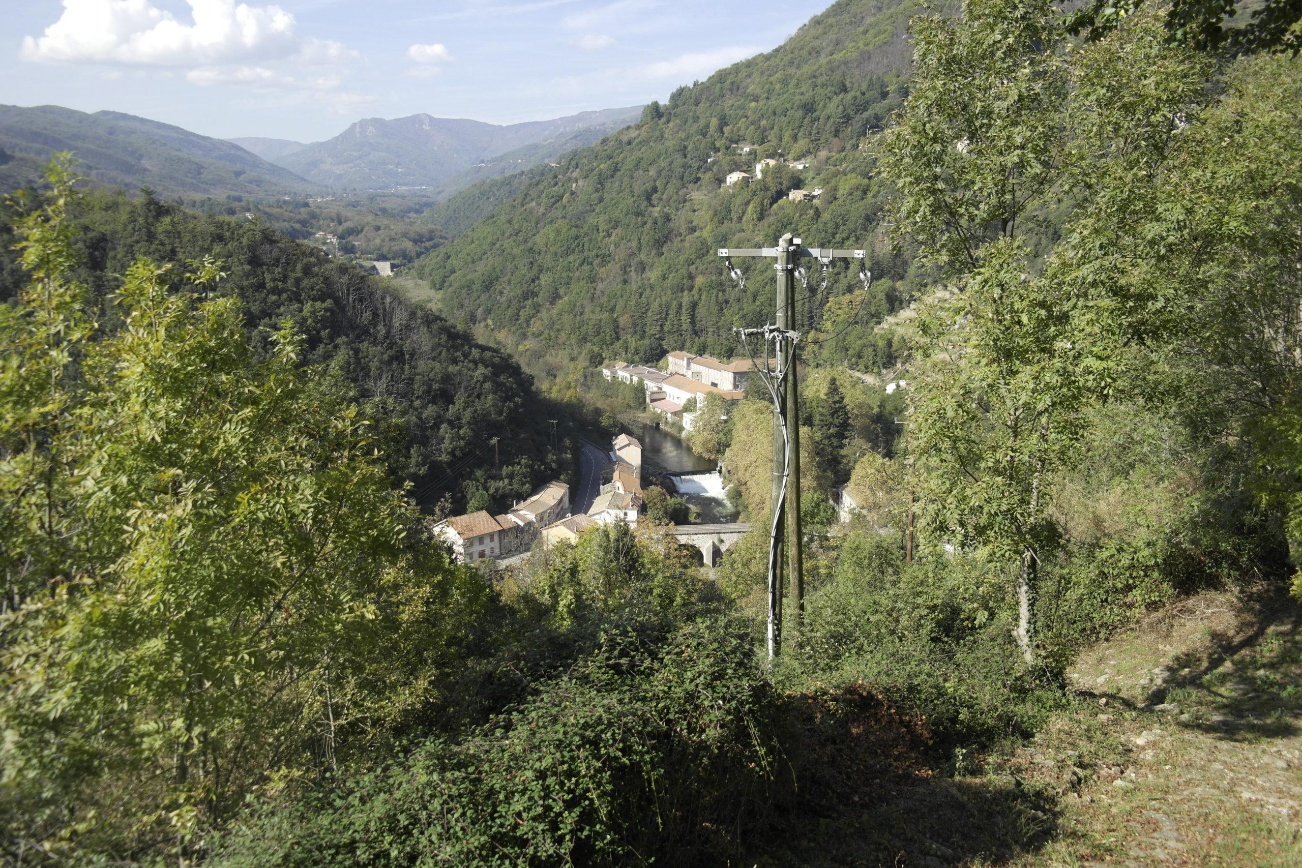 vue de loin, le moulinage est au fond de la vallée de la Fontaulière, entourée de montagnes boisées