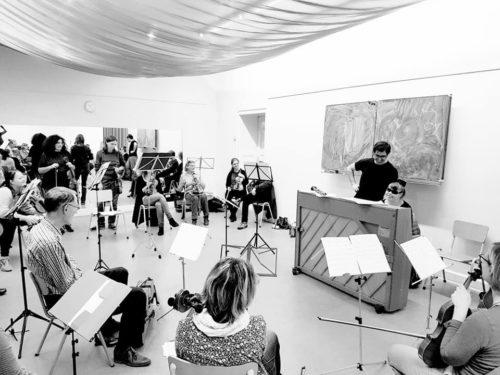 Orchester probt Stück. Man sieht ein Klavier und andere Musikinstrumente.