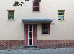 Ein rote Tür mit vertikal verlaufenden Fenstern in der Mitte, die mit einer Stufe in ein Wohnhaus führt
