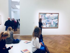 Ausstellungsansicht mit Besucher*innen. Einige sitzen im Vordergrund auf einer runden Bank. Im Mittelgrund hängt ein Gemälde an der Wand. Im linken Bildhintergrund läuft eine Gruppe in den nächsten Raum