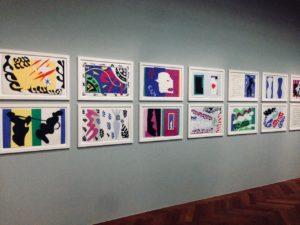 Ausstellungsansicht mit zwei Reihen übereinander gehängter bunter Papiercollagen in weißen Rahmen