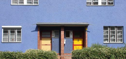 Zwei Türen, eine in braun, die andere in rot-gelb, die horizontal in drei Teile gegliedert sind, wobei das oberste Drittel aus Glas besteht und mit drei Stufen in ein blaues Wohnhaus führen