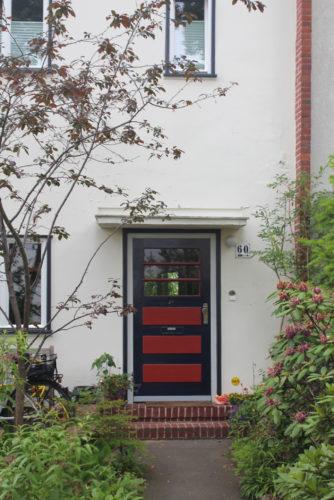 Eine Tür in schwarz und rot, die mehrfach gegliedert ist, das obere Drittel vit Fenstern versehe wurde und in ein weißes Haus führt
