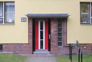 Ein rote Tür mit vertikal verlaufenden Fenstern in der Mitte und einer Backsteinrahmung, die mit einer Stufe in ein Wohnhaus führt