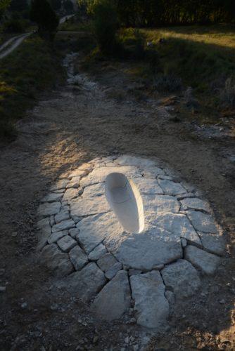 Filmstill einer weißen Steinfläche mit eineer menschengroßen Aushöhlung
