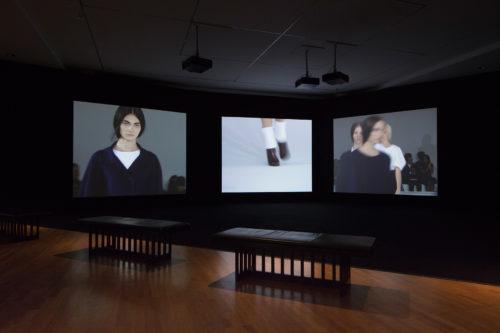 Drei Leinwandprojektionen einer Modenschau, davor drei Bänke