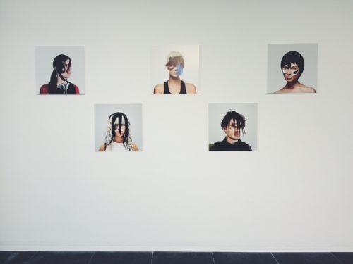 Fünf Porträtfotografien von Menschen die ausgefallene Frisuren haben und im Gesicht bunt bemalt sind um Geichtserkennungssoftware zu verwirren