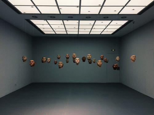 Gesichtsmodelle aus dem 3D-Drucker die mit drünnen Fänden in einen Raum gehängt sind und zu schweben scheinen