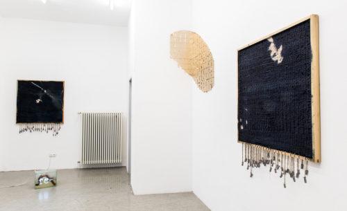 Drei Werke in der Ausstellung. Rechts wieder das Werk auf Stoff und Fäden, das an der hinteren Raumwand sein Äquivalent findet, dazwischen eine ovale Form aus Blattgold