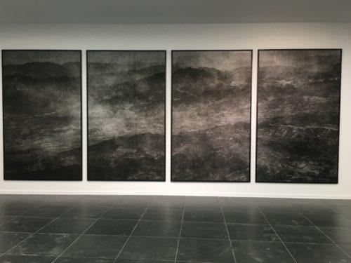 Vier Großformatige abstrake Fotografien deren Motive sich in der jeweils anschließenden Fotografie fortsetzt. Das Motiv ist dunkel gehalten und wirkt wie düstere Wolken oder der Neben zwischen dunklen Bergen