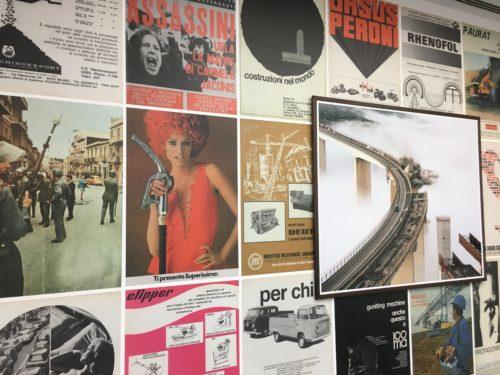 Eine mit Werbeklakaten verzierte Ausstellungswand auf der eine Fotografie angebracht wurde, auf der der Einsturz einer Brücke zu sehen ist