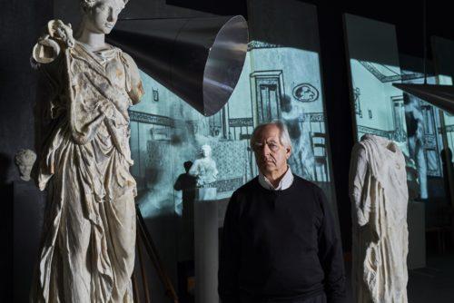 Der Künstler in der Ausstellung zwischen antiken Skulpturen, seinen Rauminstallationen und den Projektionen seiner Viedeoarbeiten an den Wänden