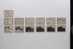 Zu sehen ist eine Aufnahme von 13 seriell hergestellten gerahmten Werken, die Computerzeichnungen zeigen. Die schwarze Fläche nimmt in Lesrichtung immer weiter zu. Die Werke hängen an einer Wand im Museum . das erste hängt linksbündig allein darunter sind zwei Reihen mit je sechs untereinander hängenden Werken  zu sehen.