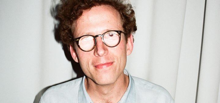 Das Foto zeigt Johann König, ein mittelalter, weißer Mann mit dunkelbloden Locken und einem hellblauen Hemd in der Frontalansicht. Er trägt eine Brille, die zum Teil verspiegelt ist und so seine Augen unkenntlich macht.