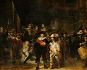 Rembrandt malt in Öl auf Leinwand eine Bürgerwache des 17. Jahrhunderts in Amsterdam. Das Bild ist sehr dunkel, im Vordergrund treten zwei Männer in den Vordergrund, die wie durch ein Schlaglicht erhellt werden.