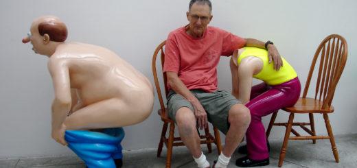 Das Bild zeigt den Künstler in rotem Shirt und grauer, kurzer Hose zwischen zwei seiner Plastikfiguren sitzen. Rechts neben ihm hockt ein weißer Mann oberkröperfrei und mit heruntergezogener, blauer Hose in Profilansicht. Er hat eine Halbglatze und stützt seine Arme auf seinen Knien ab. Links neben dem Künstler sitzt eine Figur, kopflos und ebenfalls nur von der Seite sichtbar, mit gelben Shirt und roter Hose auf einem braunen Holzstuhl. Der Künstler hat seinen Arm um den Rücken dieser Plastikskulptur gelegt.