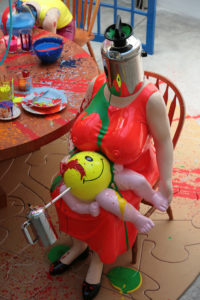 Das Bild zeigt eine kopflose, weiße Frau. Sie trägt ein grelles rotes Kleid, auf dem in Brusthöhe grüne Farbe herunterläuft. Ihre Brüste sind sehr groß und die Brustwarzen scheinen durch das Kleid. Auf dem Schoß hat sie ein Baby liegen, dessen Körper aus einem runden Ball besteht. Statt Torso und Kopf sieht man ihr einen gelben Smiley, von denen menschliche GLieder ausgehen. Über dem linken Auge verläuft rote Farbe und aus der linken Schädelhälfte geht ein dünnes Rohr hervor an dessen Ende ein kaffeemaschinen-ähnliches Objekt befestigt ist. Der am linken Bildrand befindliche Esstisch ist ebenfalls mit bunter Farbe vollgespritzt, welches sich auf der Tischplatte und dem Geschirr verteilt.
