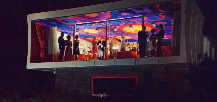 Es ist dunkel und man hat Einblick in das Loft des Plastikhauses fg2000: Man sieht den bunten Deckenteppich und die Silhouette von Dutzenden Leuten, die offenbar eine Party feiern.