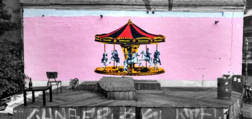 Zu sehen ist ein historisch anmutendes Kinderkarussell mit fünf an Stangen fixierten Pferdefiguren, rosafarbend hinterlegt.