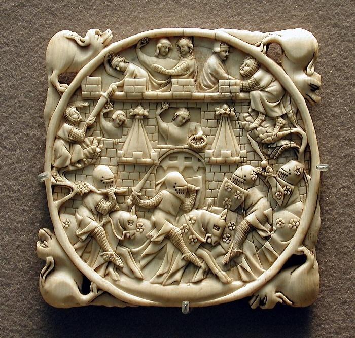 Dargestellt ist eine Ansicht der Vorderseite einer Spiegelkapsel. Die Schnitzerei in der kreisförmigen Mitte zeigt die Belagerung der Liebesburg. vier  hundeähnliche Tiere an den Eckpunkten verleihen der Kapsel eine quadratische Form .