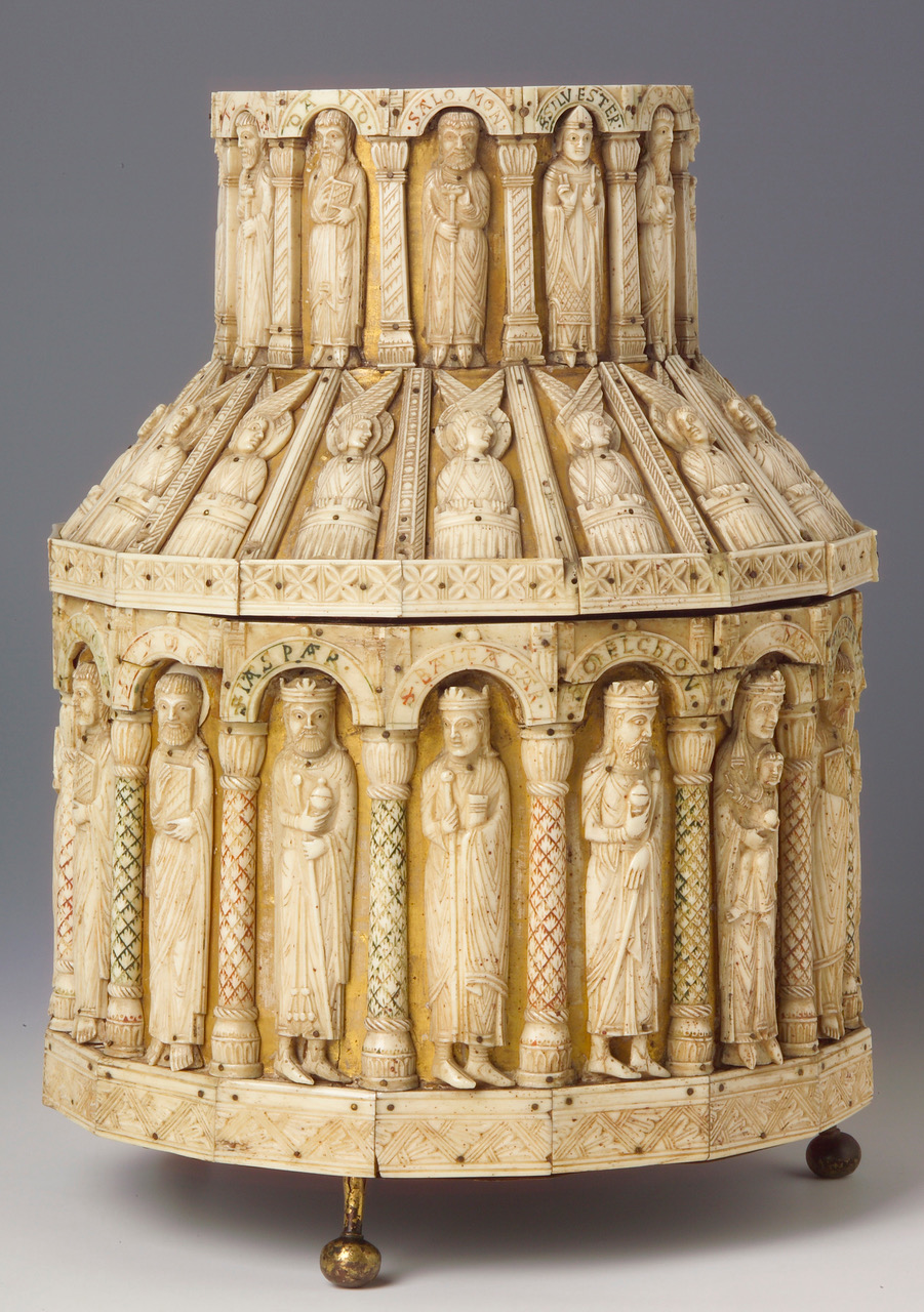 Zu sehen ist ein Turmreliquiar aus Elfenbein. Sowohl auf dem Deckel, als auch auf den runden Kastenkörper, befinden sich geschnitzte Figuren, die durch Säulenschnitzereien getrennt werden.. Das Reliquien steht auf drei Metallfüßchen.