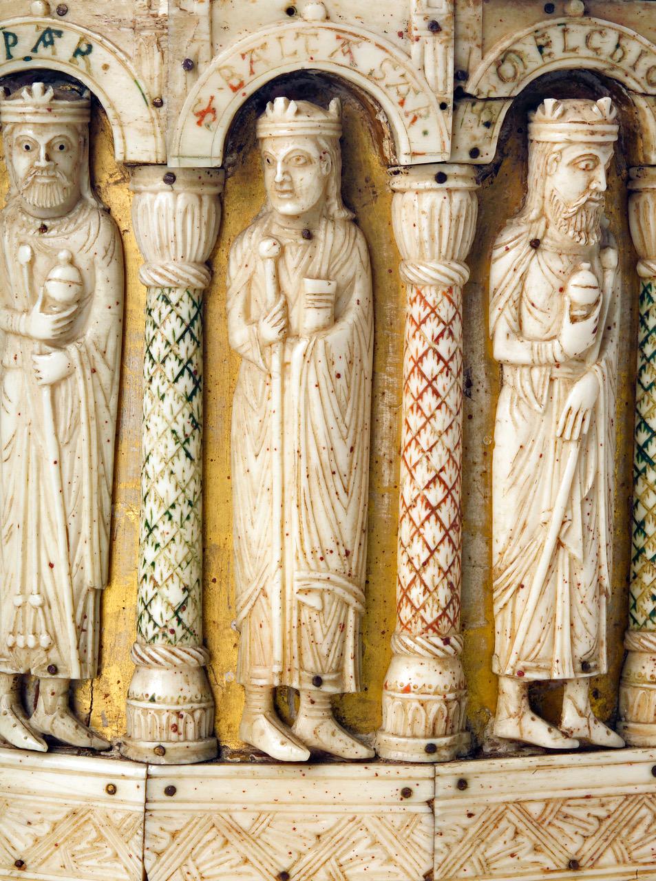 Zu sehen ist eine Detailansicht des Großen Turmreliquiars. Drei sehr fein ausgearbeiteten Elfenbeinfiguren stehen zwischen Säulen in jeweils eigenen Nischen mit Kuppeldach. Sowohl an den Säulen, als auch an der Überdachung der Nischen sind grüne und rote Farbreste erkennbar.