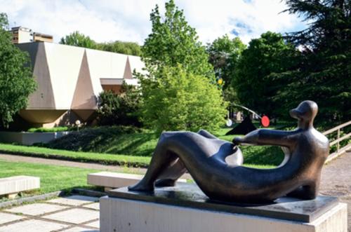 Das Bild zeigt eine Skulptur einer liegenden Figur. Ihre Körperkonturen sind sehr rund und fließend, ohne kantige Ecken. Sie besitzt einen sehr kleinen, haarlosen Kopf, der im Gegensatz zum massigeren Körper steht. Die Skulptur liegt auf einem Sockel. Im Hintergrund erkennt man einen Baum, sowie ein dahinterliegendes Gebäude.