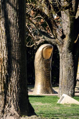 Das Bild zeigt die Skulptur eines riesigen, bronzenen Daumens mit goldenem FIngernagel, inmitten von Bäumen.