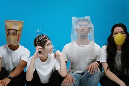 Die Fotografie zeigt vier Personen vor einem blauen Hintergrund. Sie alle tragen verschiedene Bedeckungen, die unterschiedliche Augenpartien verdecken.